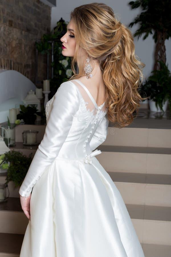 Elegant brud för härlig söt flicka i en elegant bröllopplatestoit på trappan arkivfoto