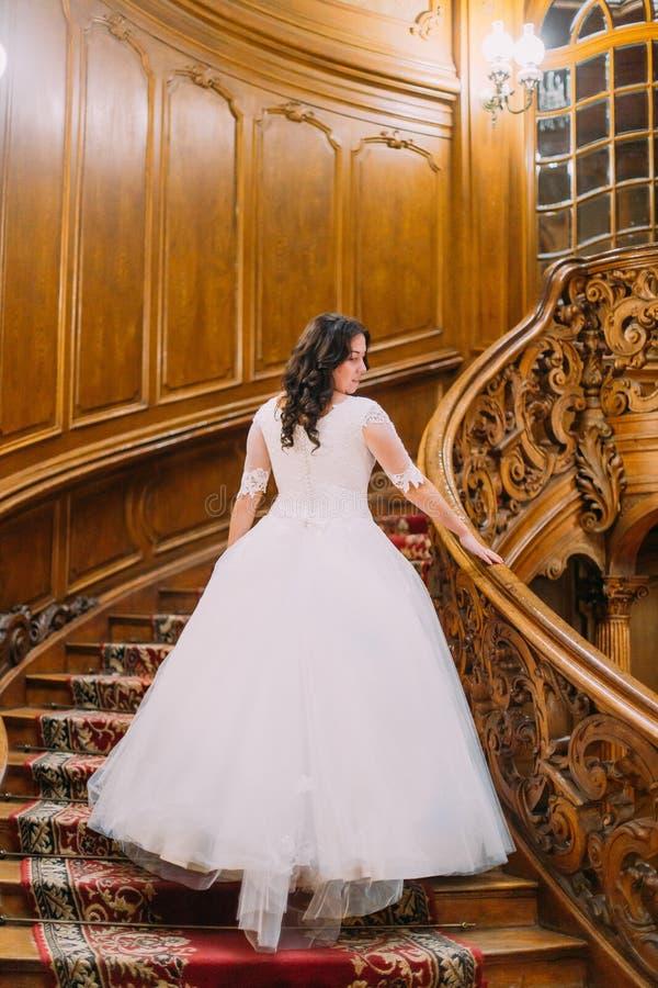 Elegant brud i den vita klänningen med den långa svansen på den gamla tappningslotten som går upp stor trätrappa royaltyfri bild