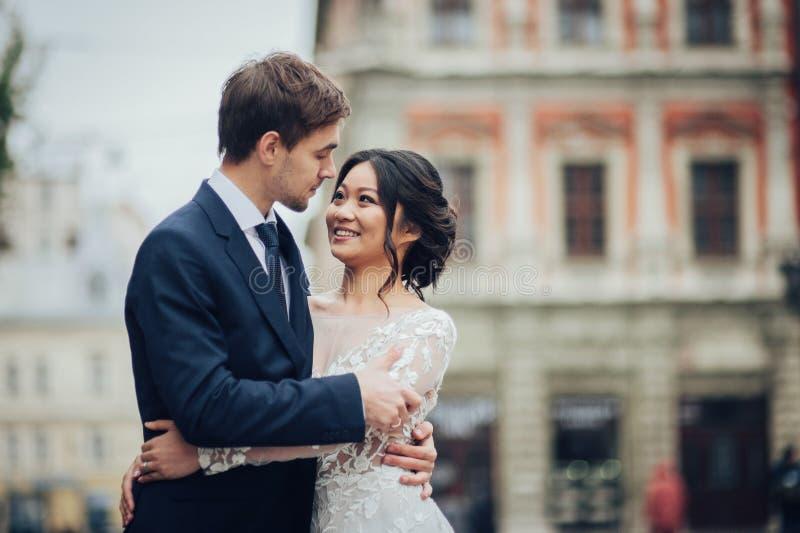 Elegant brud med brudgummen som går nära gammal katolsk domkyrka arkivbilder