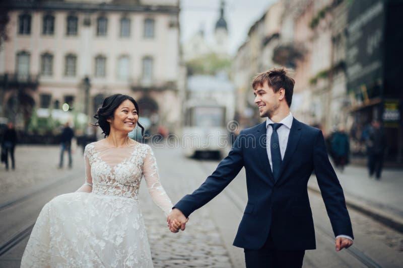 Elegant brud med brudgummen som går nära gammal katolsk domkyrka fotografering för bildbyråer