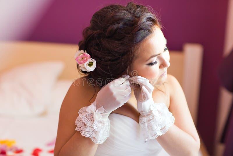Elegant brud som sätter på örhängecloseupen som förbereder sig för att gifta sig royaltyfri fotografi