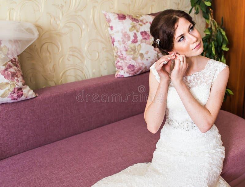 Elegant brud som sätter på örhängecloseupen som förbereder sig för att gifta sig arkivbilder