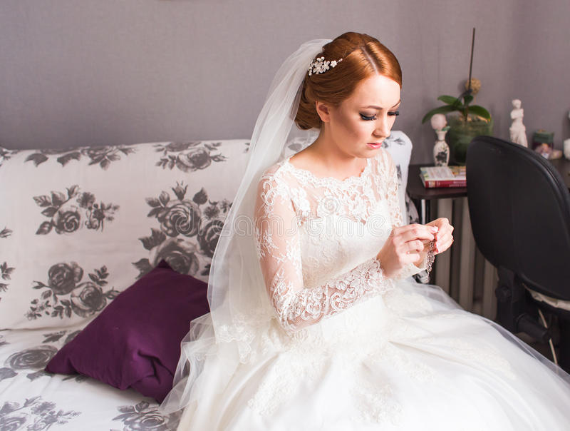 Elegant brud som sätter på örhängen som förbereder sig för att gifta sig arkivbild