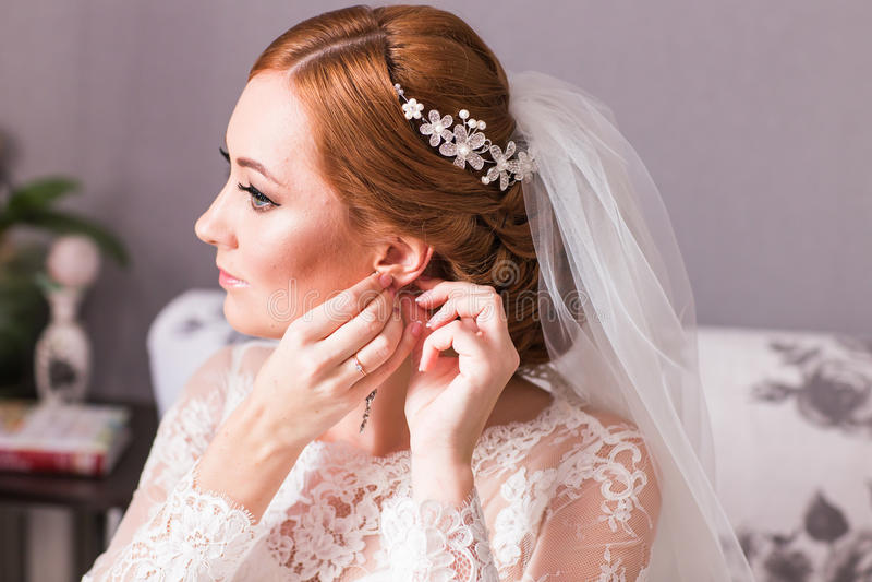 Elegant brud som sätter på örhängen som förbereder sig för att gifta sig arkivfoton