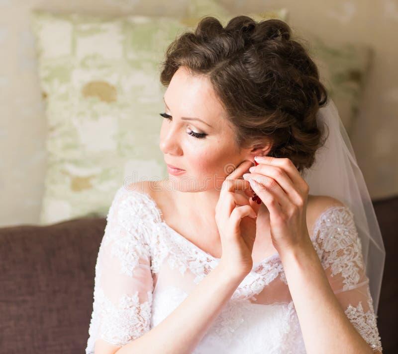 Elegant brud som sätter på örhängen som förbereder sig för att gifta sig arkivbilder