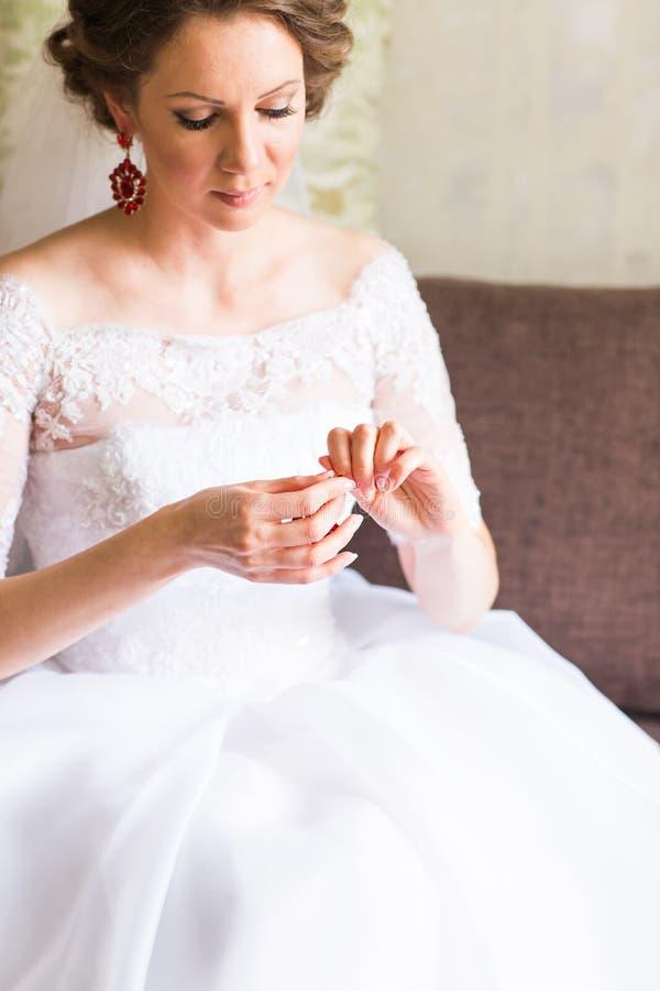 Elegant brud som sätter på örhängen som förbereder sig för att gifta sig fotografering för bildbyråer