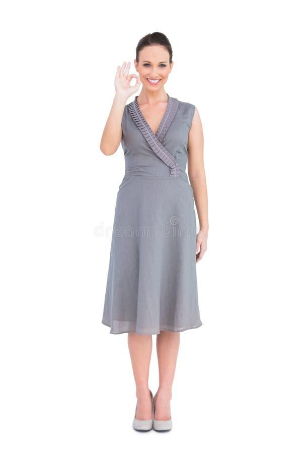 Elegant brunett i den flotta klänningen som gör en ok gest fotografering för bildbyråer