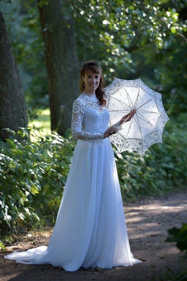 Elegant brunett i en vit klänning för tappning arkivfoton