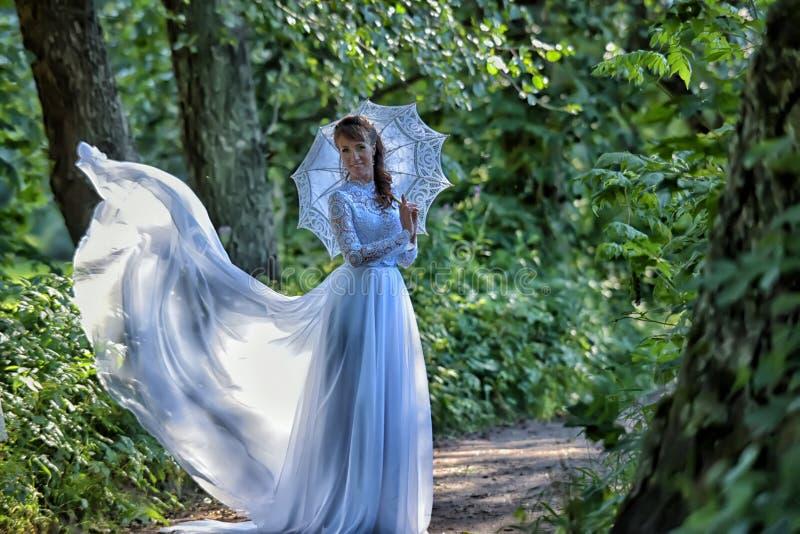 Elegant brunett i en vit kl?nning f?r tappning royaltyfria bilder