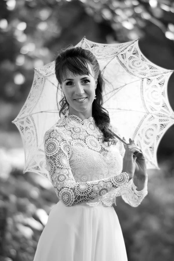 Elegant brunett i en vit kl?nning f?r tappning royaltyfri fotografi