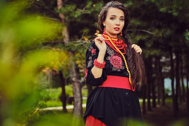 Brunette girl in a white ukrainian authentic national costume and a wreath of flowers is posing in a wood. Close-up. Elegant brunette girl with a long dark hair stock images