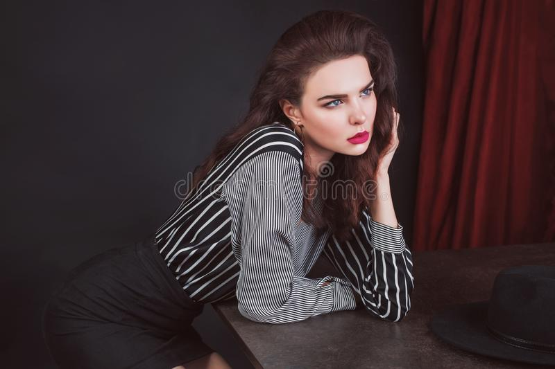 Elegant brunette girl in stylish shirt on black background. Slim tan woman in stylish clothes and red lips. Gorgeous brunette lady. With kinky hair. Elegant royalty free stock image