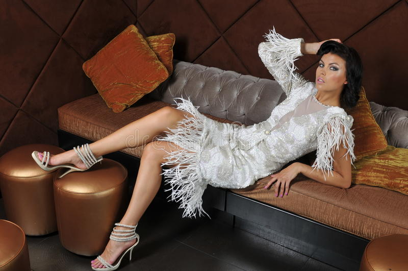 Elegant brunette model wearing couture dress. Lying on the sofa stock photos