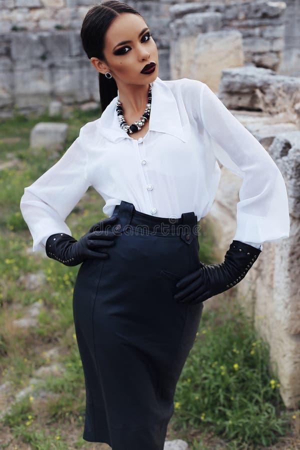 Elegant brunette wears white shirt, leather skirt and gloves royalty free stock image