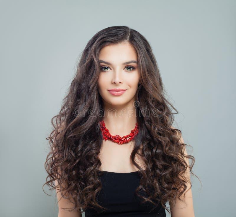 Elegant brunettkvinnamodell med makeup, lockigt långt hår och halsbandet för röd korall royaltyfri fotografi