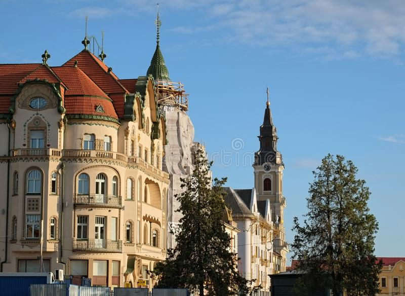 Elegant buildings and bell tower of St. Ladislaus Roman-Catholic Church in Union Square of Oradea. stock images
