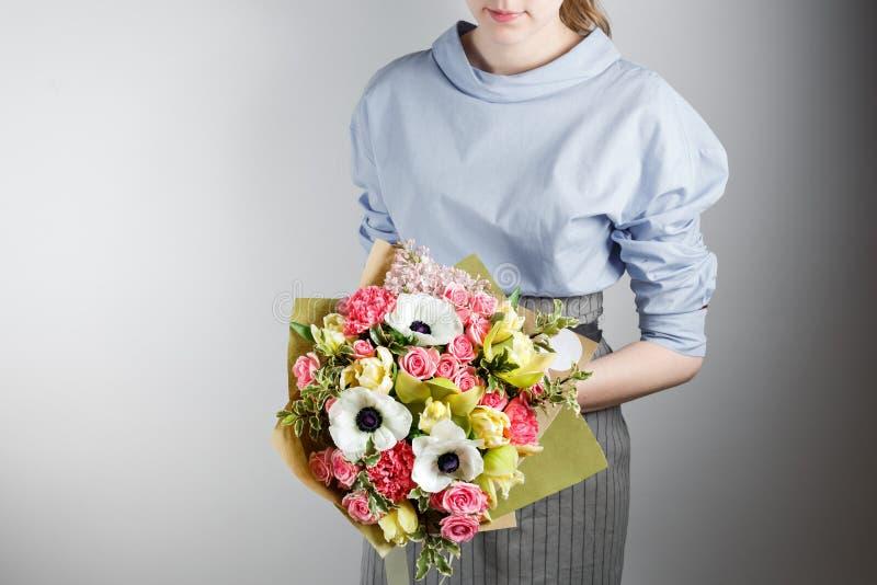 Elegant bukett av nejlikan, orkidé, rosor, anemon i hand En gullig mjuk bukett av exotiska blommor royaltyfri foto
