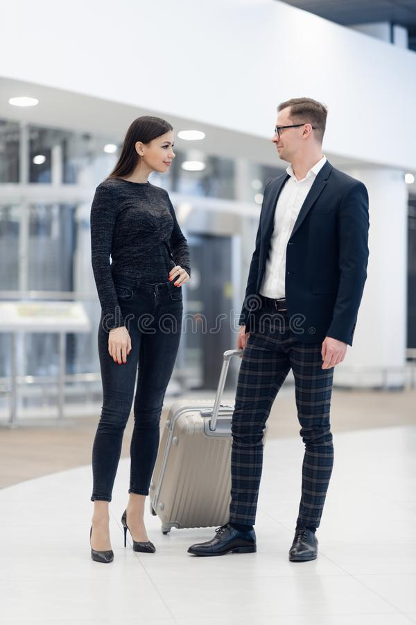 Elegant business couple standing with suitcase and airplane tickets at the waiting hall in the airport. Business travel royalty free stock photos