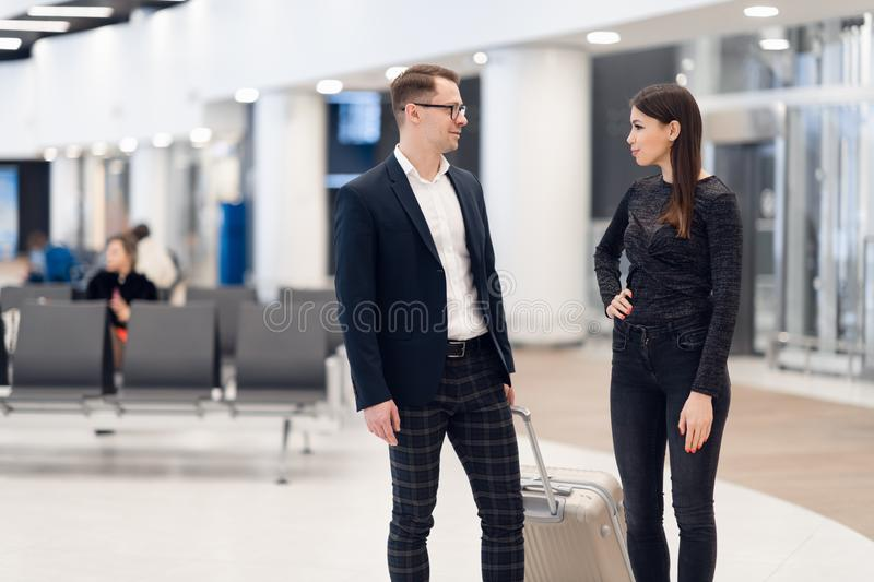 Elegant business couple standing with suitcase and airplane tickets at the waiting hall in the airport. Business travel stock image
