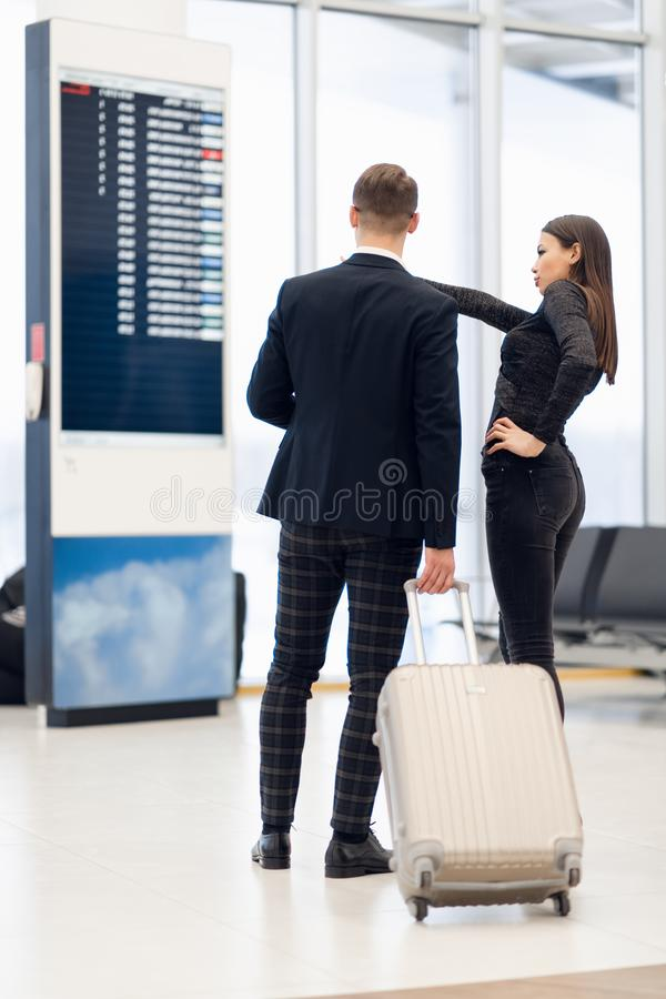 Elegant business couple standing with suitcase and airplane tickets at the waiting hall in the airport. Business travel stock photography