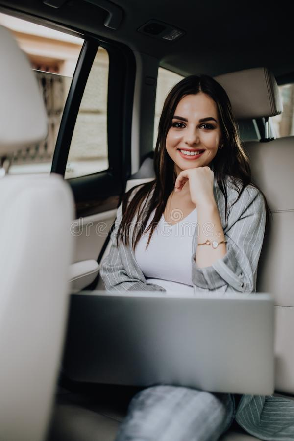 Elegant business woman sitting in car and working on laptop stock image