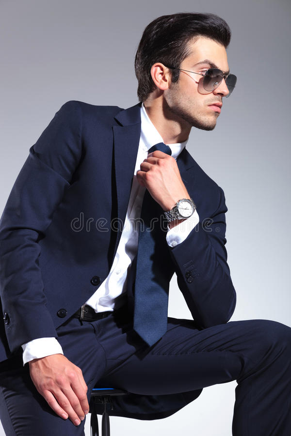 Elegant business man sitting while fixing his tie royalty free stock images