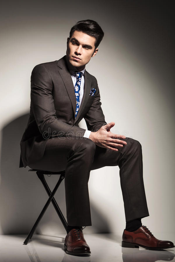 Elegant business man sitting and looking to his side. Full body image of a young elegant business man sitting on a stool againt studio backgroud, looking to his stock image