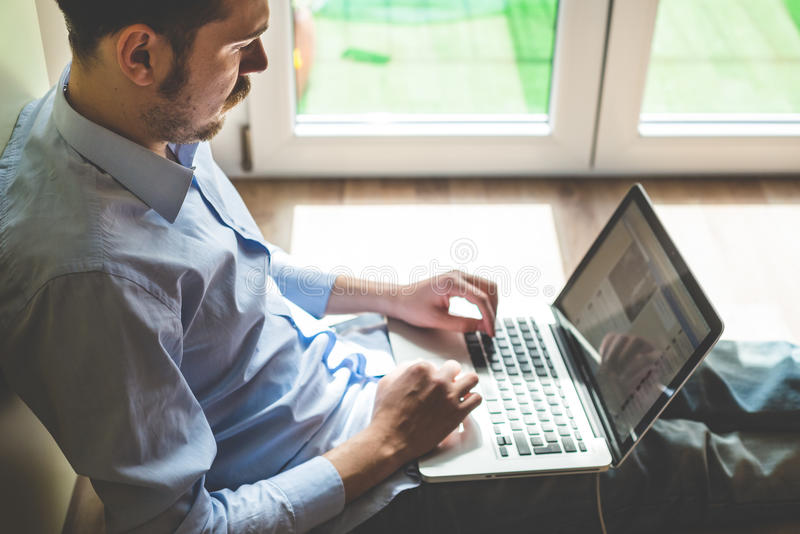 Elegant business multitasking multimedia man. Using devices at home royalty free stock images