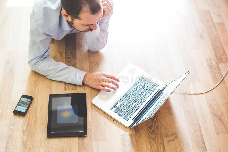 Elegant business multitasking multimedia man. Using devices at home royalty free stock photography