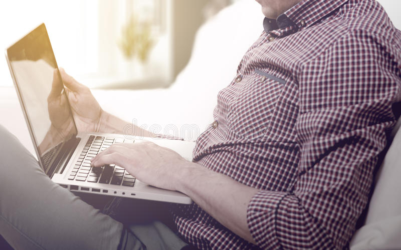 Elegant business multitasking multimedia man using devices at home.  royalty free stock photography