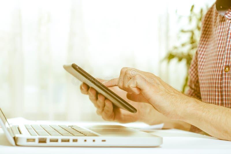 Elegant business multitasking multimedia man using devices at home.  stock images