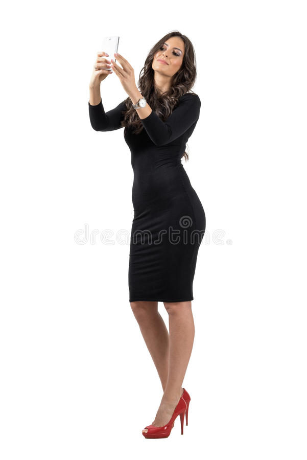 Elegant business woman in black dress talking selfie with cellphone stock images