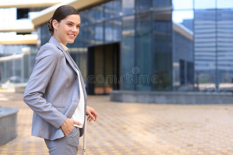 Elegant business woman with luggage in airport. Businesswoman with suitcase going to business trip royalty free stock images