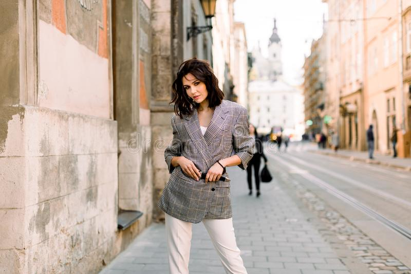 Elegant business woman wearing stylish jacket and white pants at summer day morning in the city street stock photo