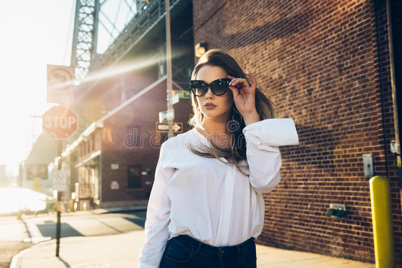 Elegant business woman wearing sunglasses and white t-shirt at hot summer day in the city. Elegant business woman wearing sunglasses and white t-shirt at hot stock photography