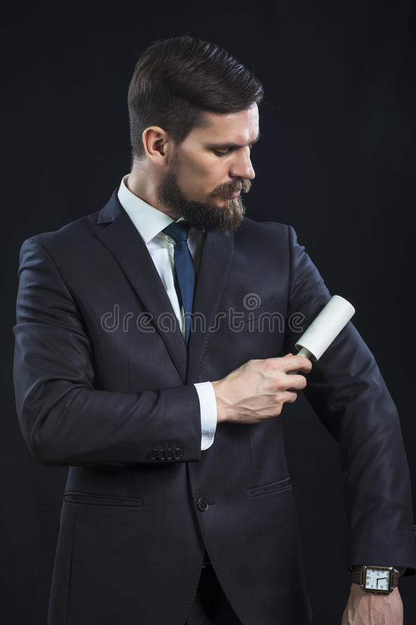 Elegant businessman cleans his suit royalty free stock photography