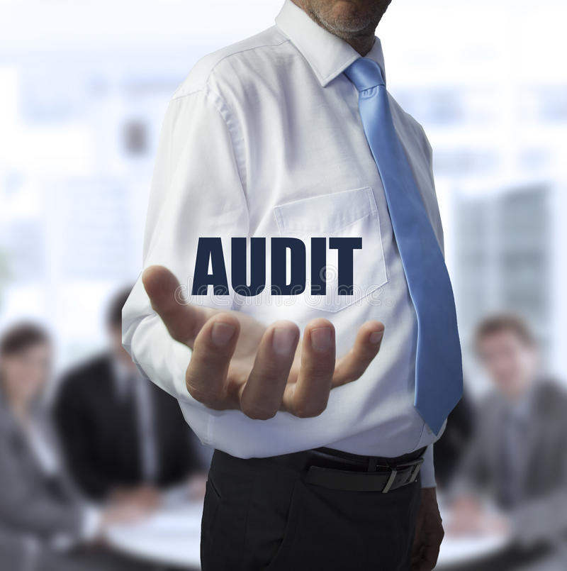 Elegant businessman holding the word audit. In front of a business team stock photos