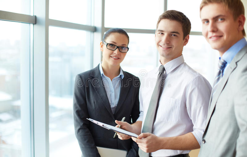 Elegant businessman. Image of three employees looking at camera, focus on elegant men with clipboard stock photos