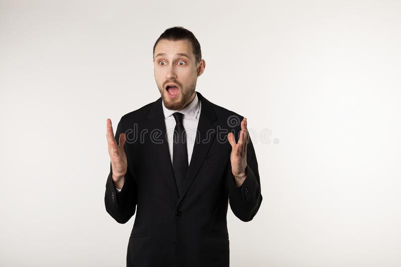Elegant businessman over  white background clueless and confused expression hands raised stock photos