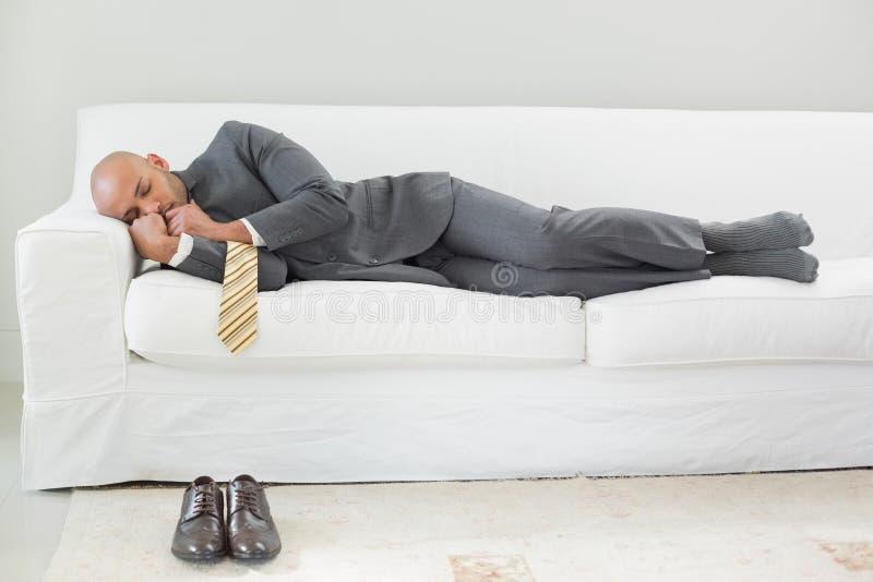 Elegant businessman sleeping on sofa. Full length of an elegant businessman sleeping on sofa at home royalty free stock photography