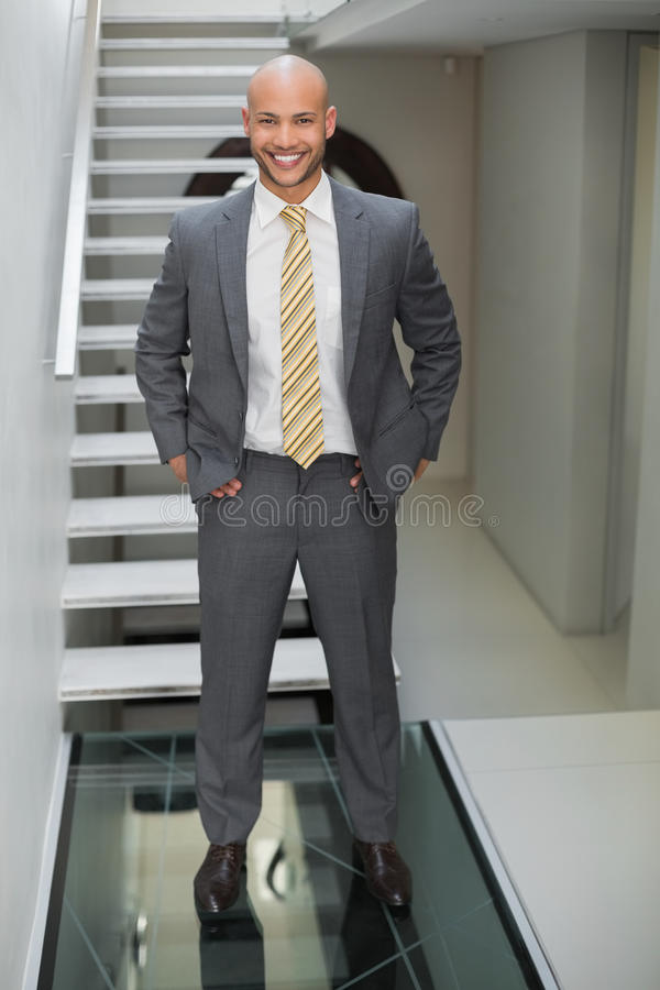 Elegant businessman standing against staircase in office. Portrait of a smiling elegant young businessman standing against staircase in office royalty free stock photography
