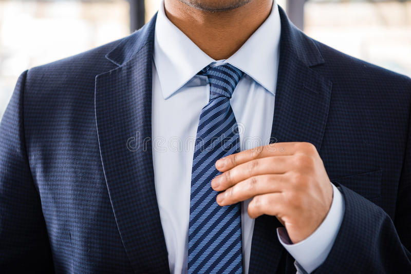 Elegant businessman in suit tying necktie royalty free stock photos