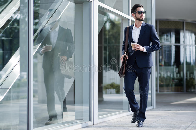 Elegant businessman. With take-out coffee going to work stock image