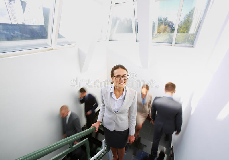 Elegant businesswoman. Portrait of smart businesswoman looking at camera on background of other people ascending and descending staircase stock photo
