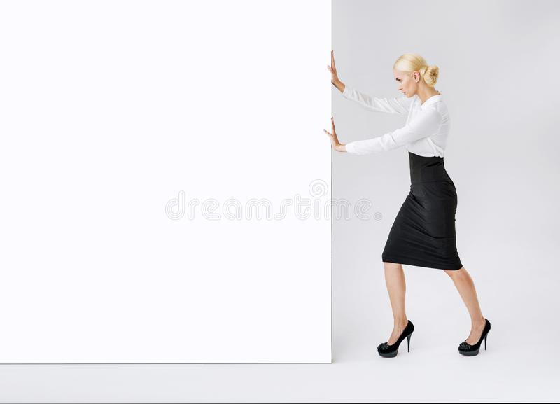 Elegant businesswoman pushing a giant empty board royalty free stock images