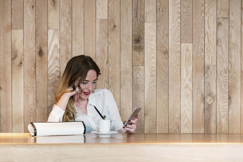 Elegant businesswoman writing text with a smartphone in a restau stock photography