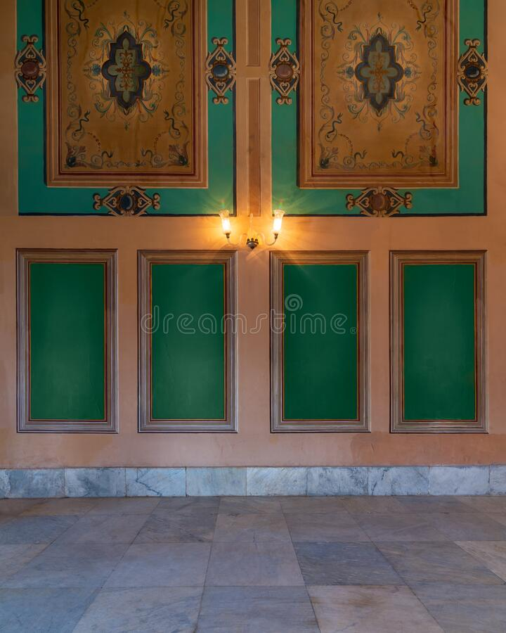 Elegant carved green frames on orange wall with ornate border and lanterns over marble floor. Beautiful elegant carved green frames on orange wall with ornate royalty free stock image