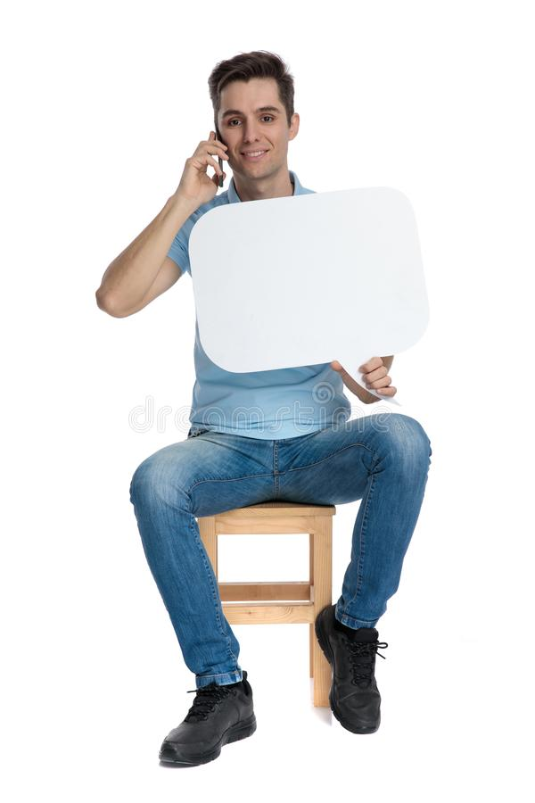 Elegant casual man talking on his phone, holding a sign stock images