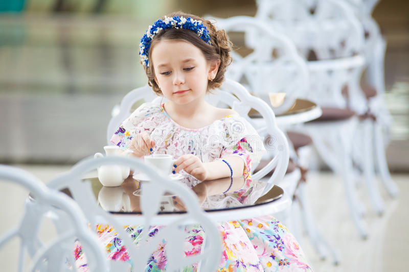 Elegant child girl in a floral dress drinking tea stock images