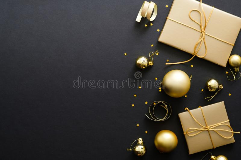 Elegant Christmas background with modern golden Christmas decorations, baubles, gift boxes, confetti stars on dark black backdrop. Flat lay design, top view stock photography